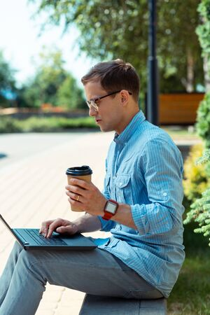 Reading e-mails. Businessman enjoying coffee break outside and reading e-mails in the park