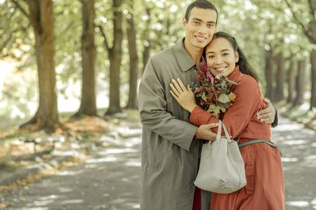 Pleased good-looking girl. Sweet good-looking couple tightly hugging each other and having wide smiles
