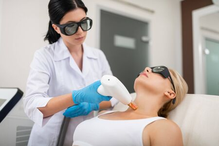 Photo pour Coming down. Blond woman lying in the cosmetologists office getting her neck skin laser treatment. - image libre de droit