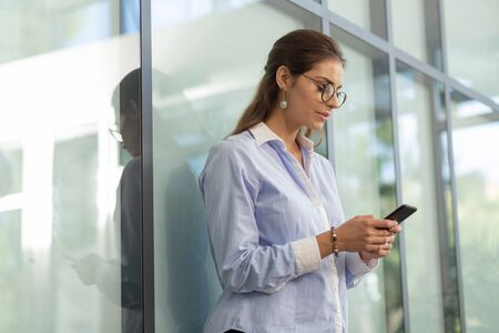 Photo pour Online chat. Concentrated brunette girl standing near glass wall while checking her email in telephone - image libre de droit