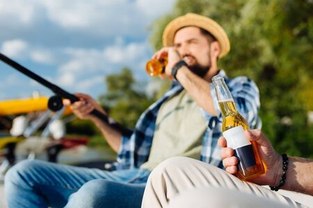Photo pour Drinking beer. Dark-haired bearded handsome son drinking bottle of beer while fishing with dad - image libre de droit