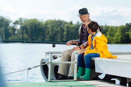 Foto de Listening to grandfather. Dark-haired schoolboy listening to his bearded grandfather while fishing - Imagen libre de derechos