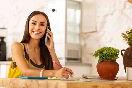 Call from husband. Cheerful entrepreneur smiling while receiving call from husband