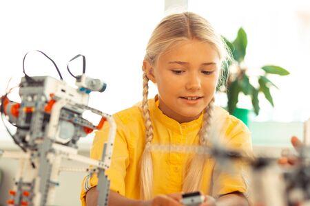 Photo pour Future scientist. Smiling schoolgirl sitting at her desk during science lesson building a construction set model. - image libre de droit