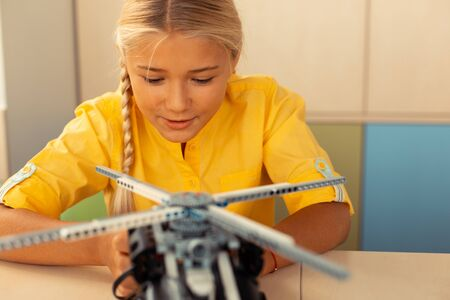 Photo pour Trying new. Enthusiastic schoolgirl sitting at the desk in the classroom beginning launching a helicopter model. - image libre de droit
