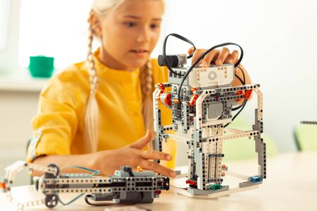 Photo pour Glad to learn. Enthusiastic girl sitting at the school desk and building a robot using construction set during her science lesson. - image libre de droit