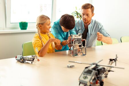 Photo pour Lending a helping hand. Enthusiastic boy standing between his teacher and classmate sitting at the school desk helping a girl building her robot. - image libre de droit