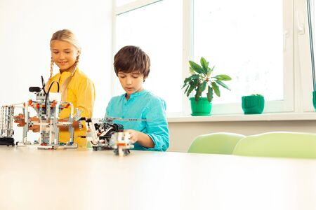 Photo pour Little inventors. Concentrated boy and happy girl sitting in the classroom with their models made of construction set preparing for their first science exhibition. - image libre de droit