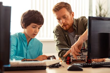 Photo pour Helping to improve. Serious teacher showing a concentrated pupil building a robot out of construction set his mistakes in the project. - image libre de droit