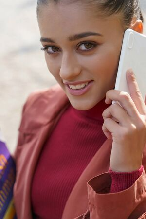 Photo for Close-up picture of a good-looking young woman with a smartphone near her ear - Royalty Free Image