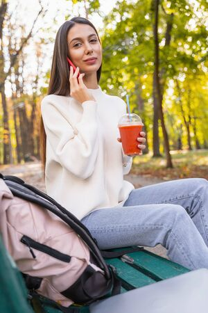 Have a break. Pleased young woman talking per telephone and looking straight at camera