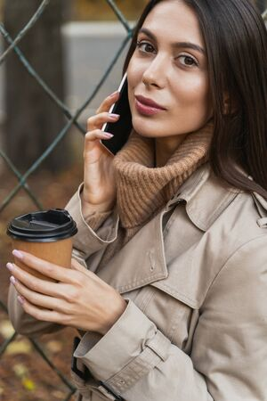 I am here. Pleased brunette keeping smile on her face while talking per telephone