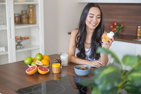 Photo pour Smiling girl with a bottle of vitamins sitting at the kitchen table - image libre de droit