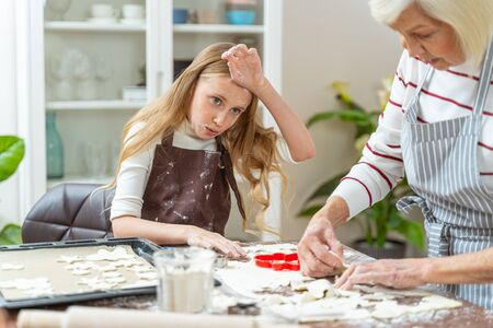 Photo pour Tired young female baker sitting at the kitchen table - image libre de droit