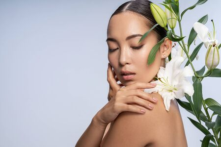 Foto de Sexy woman smelling flowers. Female beauty concept - Imagen libre de derechos
