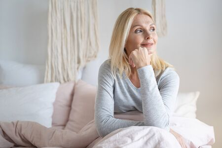 Photo for Calm smiling woman thoughtfully looking away with her hand touching her chin - Royalty Free Image