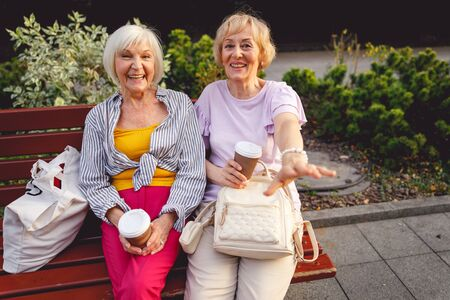 Photo for Happy aged ladies laughing and having coffee sitting on a bench - Royalty Free Image