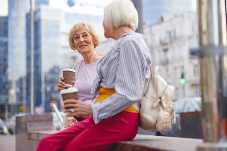 Photo for Two beautiful old ladies sitting and drinking coffee in the city centre - Royalty Free Image