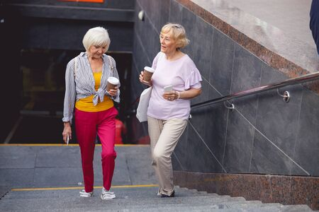 Photo for Two aged ladies going out the underpass and drinking coffee - Royalty Free Image
