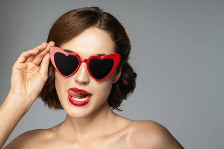 Photo pour Playful mood. Beautiful girl touching her glasses while looking at camera - image libre de droit