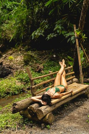 Follow me. Pleased brunette female person wearing swimsuit for sunbathing, enjoying sounds of exotic nature