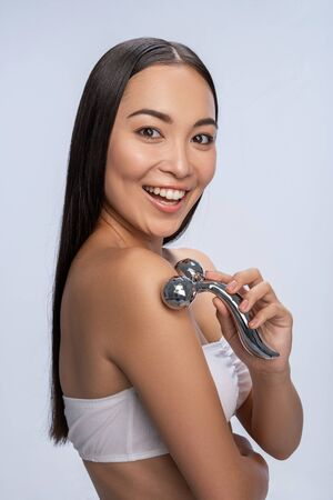 Photo pour Waist up of happy Asian female massaging her skin with platinum massage roller. Isolated on white background. Clear skin concept - image libre de droit