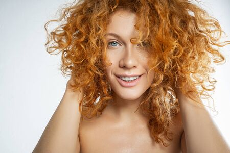 Photo pour Portrait of a cheerful young Caucasian female touching her curly red hair with both hands - image libre de droit