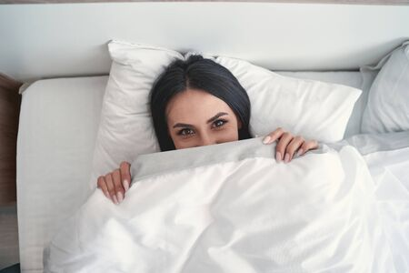 Photo for Playful mood. Delighted young woman lying in her bed and looking straight at camera - Royalty Free Image