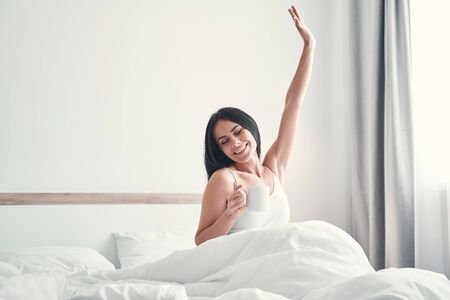 Enjoy the moment. Pleased brunette girl sitting on the bed and demonstrating her smile