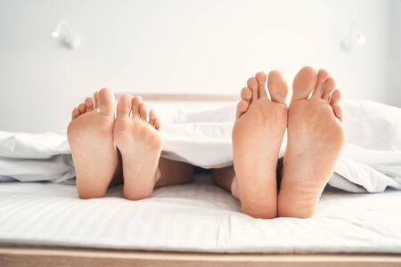 Photo for Close up of two pairs of bare feet of the married Caucasian couple lying under the blanket - Royalty Free Image