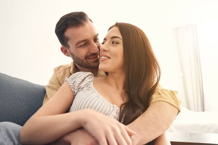 Photo pour Close up of happy young man and woman embracing on a soft couch in living room - image libre de droit