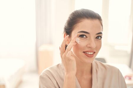 Photo pour Smiling cheerful lady spending time with beauty procedures at home in the morning while using gentle eye cream - image libre de droit