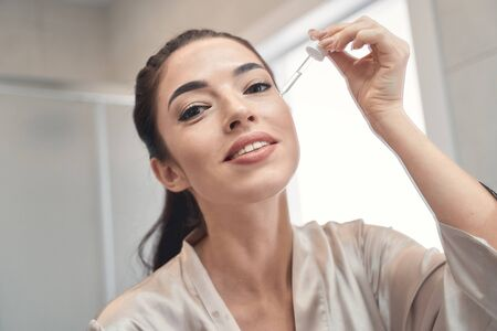 Photo pour Happy pretty female in a dressing gown preparing to put eye serum at beginning of the day - image libre de droit
