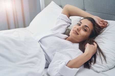 Photo pour Attractive lady looking at camera and smiling while resting in bedroom - image libre de droit