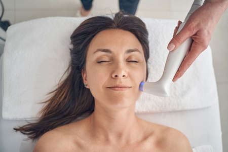 Photo pour Mirthful woman lying on soft towel and smiling with closed eyes while a cosmetologist touching her face with a low level laser hand probe - image libre de droit