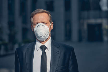 Photo for Elegant gentleman in medical face mask looking at camera while spending time outdoors - Royalty Free Image