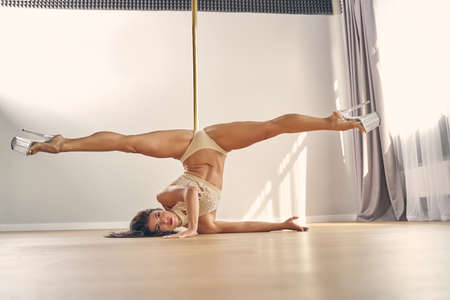 Photo pour Beautiful female dancer with perfect body wearing high heels and lingerie while doing acrobatic pose near pylon - image libre de droit