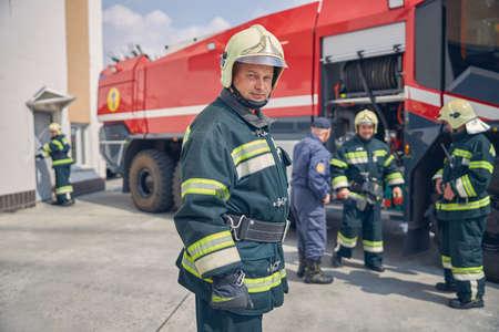 Foto für Close up portrait of man in yellow helmet standing at the outdoors in front of team firefighters - Lizenzfreies Bild
