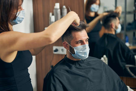 Photo pour Pretty hairdresser standing in semi position and creating stylish haircutting for her visitor - image libre de droit