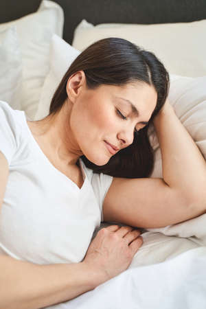 Photo pour Placid lovely Caucasian long-haired woman with her eyes shut lying on her side in bed - image libre de droit