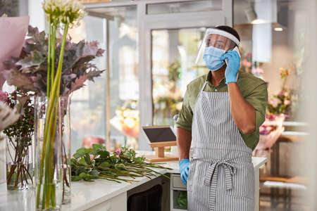Photo for Young man in protective glass and mask is making call while making bouquets in flower shop - Royalty Free Image