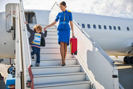 Photo pour Cabin attendant wearing a blue outfit helping a small boy with an identity form in getting off the plane - image libre de droit