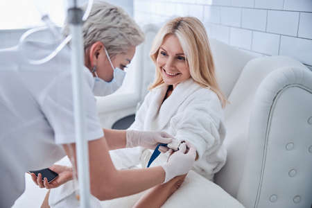 Photo pour Side view portrait of happy cheerful talking with professional doctor while receiving IV infusion in beauty clinic - image libre de droit