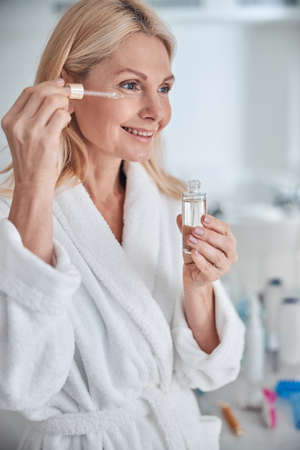 Photo pour Close up portrait of happy smiling woman applying facial oil or serum with pipette in bathroom - image libre de droit