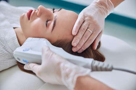 Photo pour Relaxing charming female in white bathrobe enjoying ultrasound contour face plastic in spa center - image libre de droit