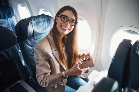 Photo pour Happy lady sitting near plane window while holding box - image libre de droit