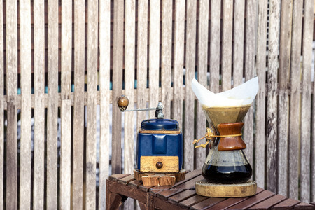 Photo pour metal coffee grinder and drip glass pitcher on old wooden background - image libre de droit