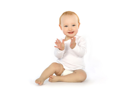 Photo for Pretty baby in white shirt claps his hands - Royalty Free Image