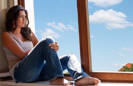Young woman daydreaming on a beautiful day, sits by a window