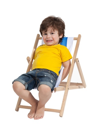Photo pour Adorable Toddler boy sitting on deck chair, isolated on white - image libre de droit